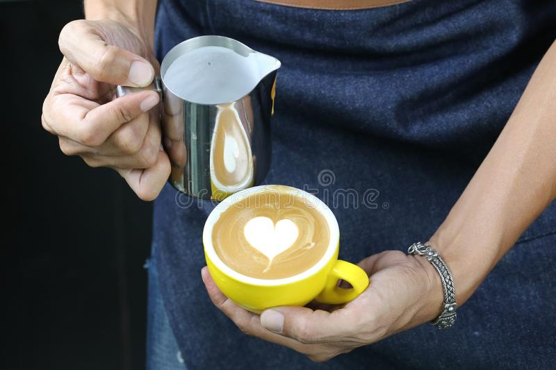 Barista pouring milk foam for making coffee latte art with pattern the heart in a cup royalty free stock images