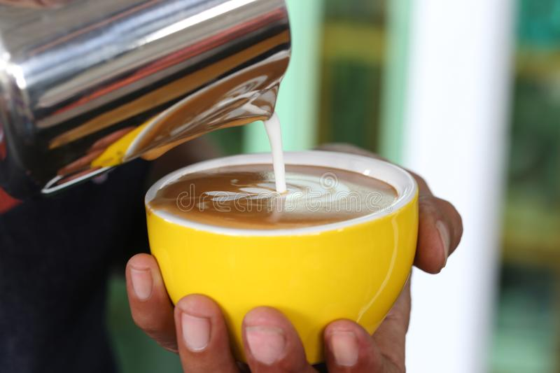 Barista pouring milk foam for making coffee latte art with pattern the leaves in a cup royalty free stock photography