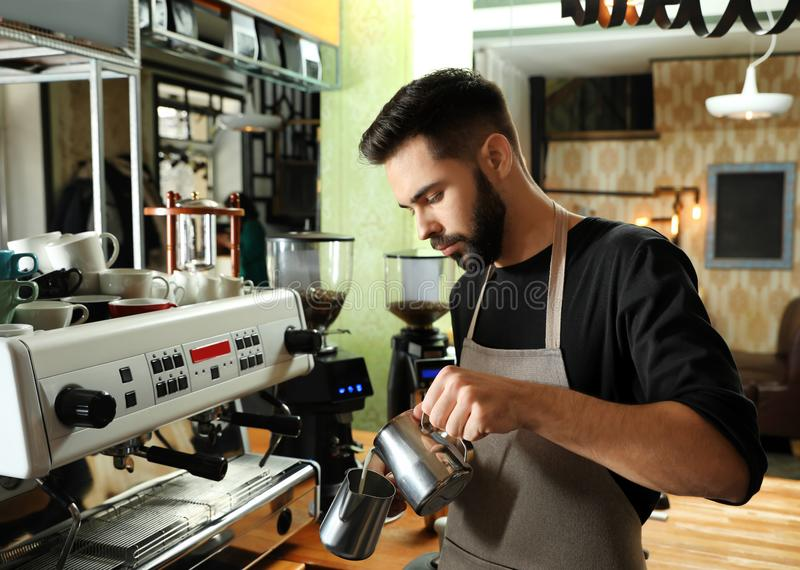 Barista pouring milk into metal pitcher near coffee machine. At bar stock photography