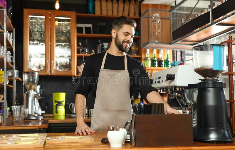 Barista pouring milled coffee from grinding machine into portafilter stock photos