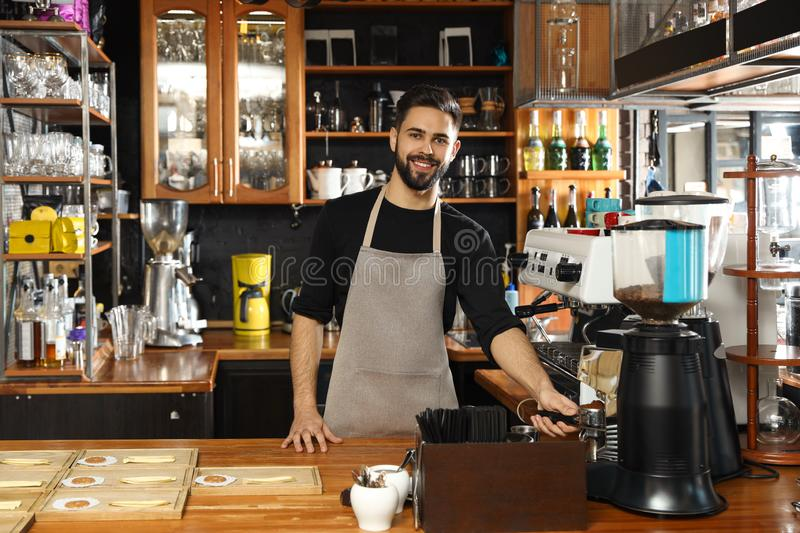 Barista pouring milled coffee from grinding machine into portafilter royalty free stock image