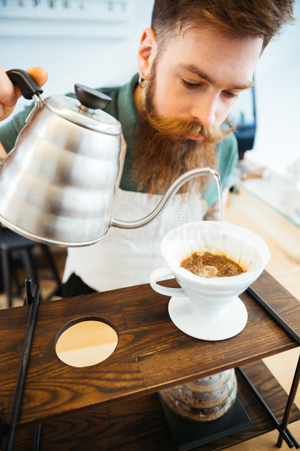 Barista pouring water on coffee ground with filter. In coffee shop royalty free stock image