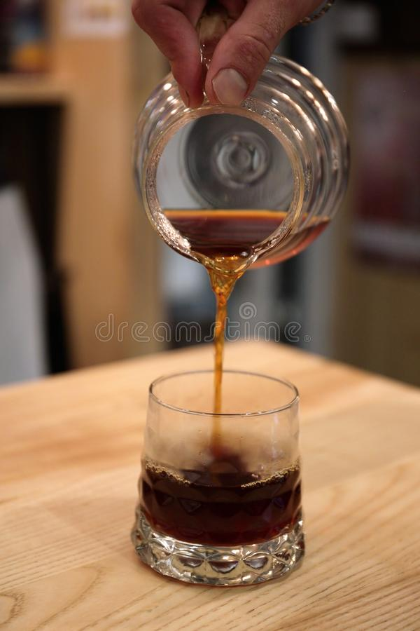 Barista pours a coffin into the glass cup serves a drink. Kemex stock images