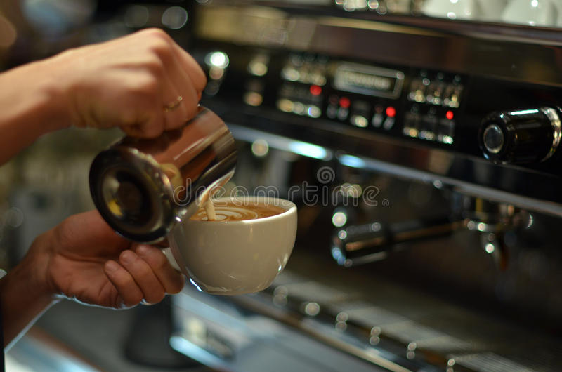 Barista prepares coffee latte. Against the background of a coffee machine. Barista at work, pours milk in a latte. Draws milk. Prepares coffee for serving. In stock photography