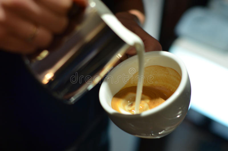 Barista prepares coffee latte. Barista at work, pours milk in a latte. Prepares coffee for serving royalty free stock photos
