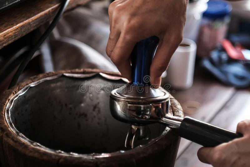 Barista presiona el café molido foto de archivo