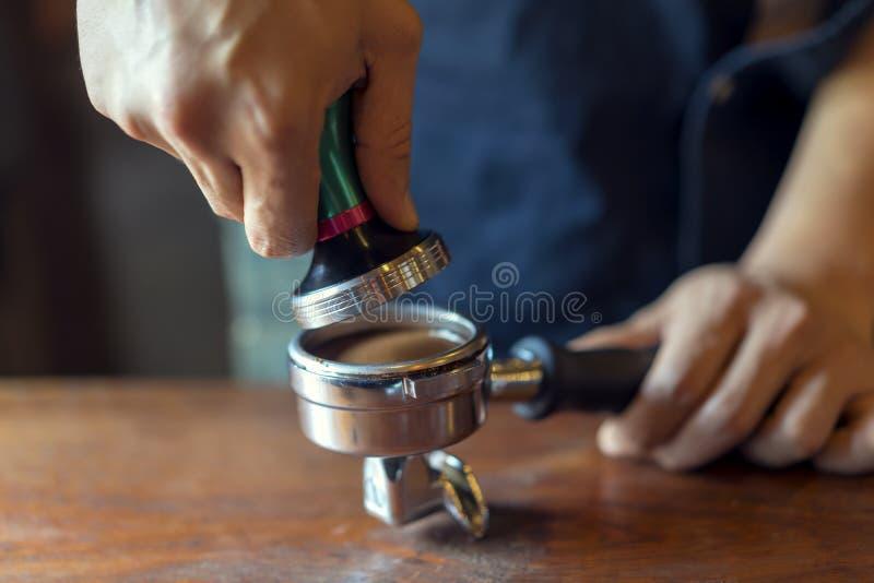 Barista presiona el café molido usando el pisón, prepara el café express en su cafetería fotos de archivo libres de regalías