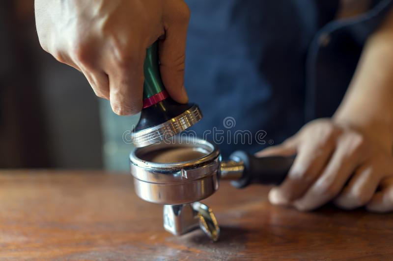 Barista presses ground coffee using tamper, prepares espresso in his coffee shop royalty free stock photos