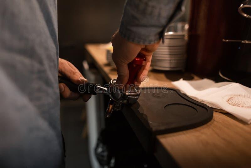 Barista profesional del hombre que presiona el café molido usando un pisón en una cafetería Tiempo del café Descanso para tomar c foto de archivo