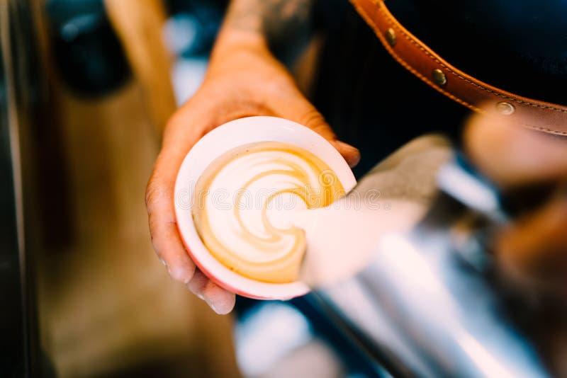 Barista profesional, hombre que hace arte del latte del café con café express y leche de la espuma fotos de archivo