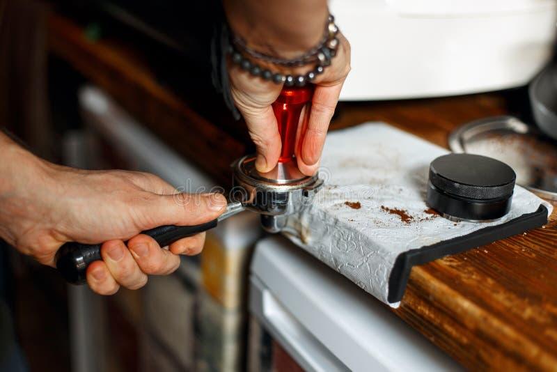Barista profesional que prepara el café en su funcionamiento de la cafetería fotografía de archivo