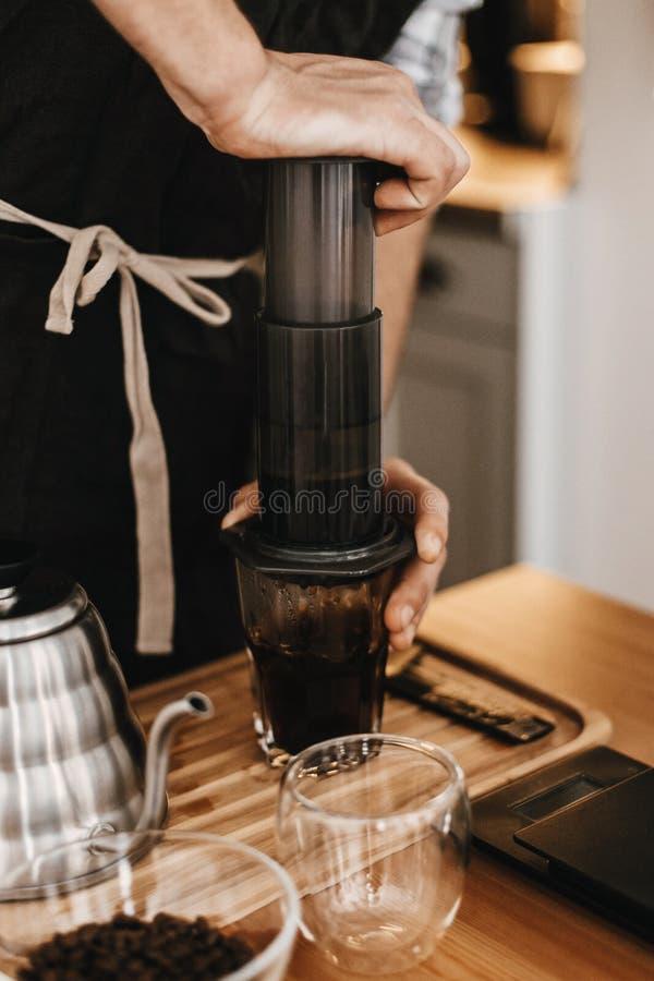 Barista profesional que prepara el café por el método alternativo de los aeropress, preparando proceso Manos en los aeropress y l imágenes de archivo libres de regalías