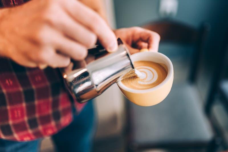 Barista profesional que vierte espuma caliente de la leche y que crea arte del latte del café foto de archivo libre de regalías