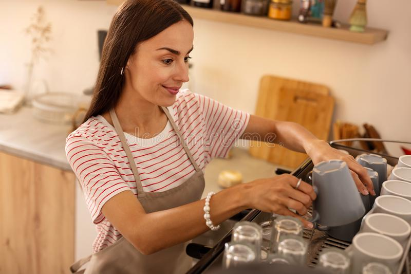 Barista putting cups on coffee machine after washing them stock images