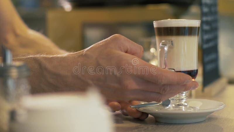 Barista que coloca o latte preparado do café no copo de vidro sobre a tabela no fim do café imagem de stock royalty free