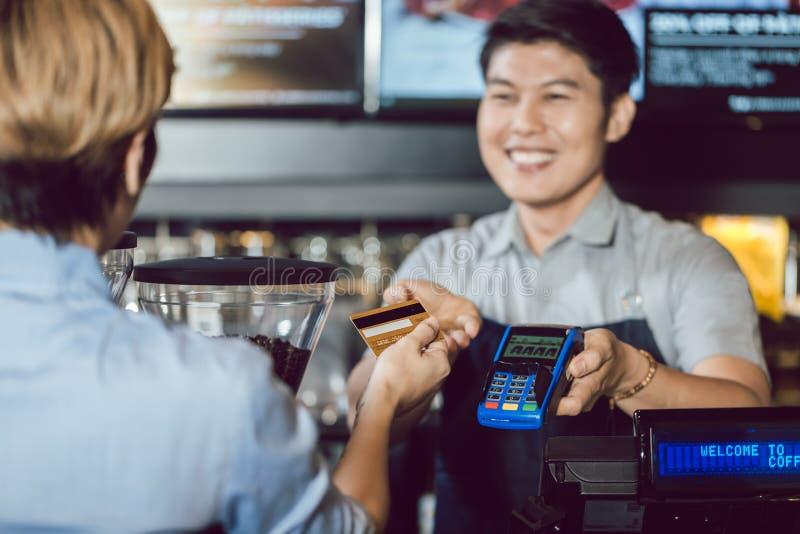 Barista que dá o serviço do pagamento para o cliente com cartão de crédito fotos de stock royalty free