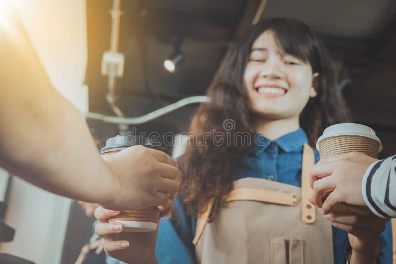 Barista que da el café al cliente en su tienda Foco selectivo imagenes de archivo