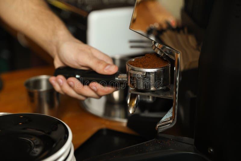Barista que derrama o café moído da máquina de moedura no portafilter foto de stock