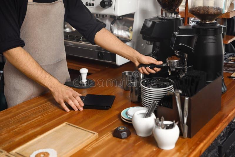 Barista que derrama o café moído da máquina de moedura no portafilter no contador da barra fotografia de stock royalty free
