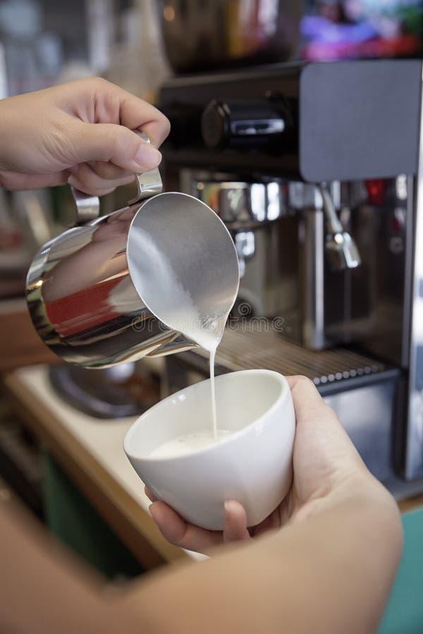 Barista que faz o cappuccino em seu coffeeshop ou caf?, close-up fotografia de stock royalty free