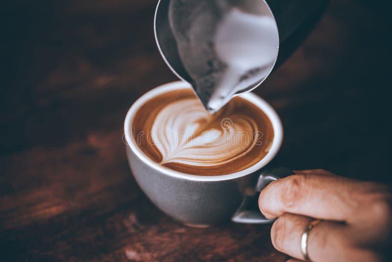 Barista que faz o leite de derramamento do córrego com forma do coração do teste padrão da arte do latte do café fotografia de stock
