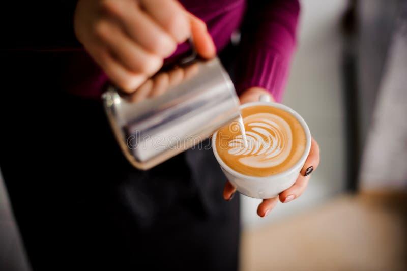 Barista que hace un arte de la leche en la taza de café express imagen de archivo
