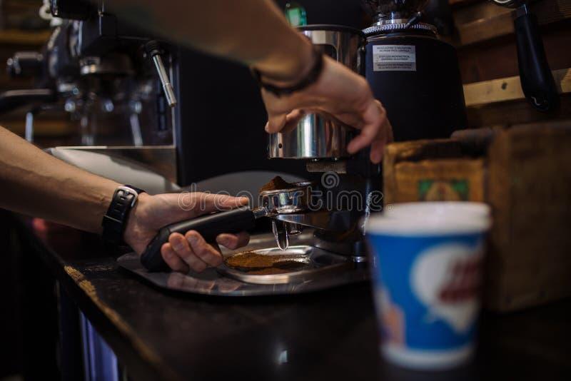 Barista que muele el café fresco en la bayoneta imagen de archivo