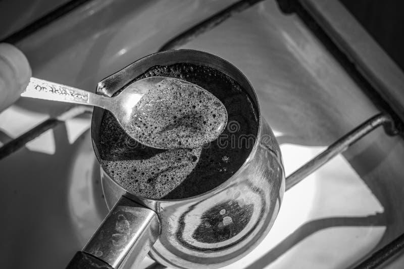 Barista que prepara a bebida saboroso quente do turco de cobre, ferve a água para o café no fogo pequeno no cezve Turco do caf fotos de stock royalty free