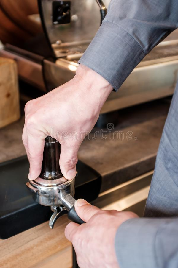 Barista que presiona el café con el pisón en portafilter a la fabricación especialmente imagenes de archivo