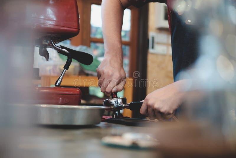Barista que presiona el café en el tenedor de la máquina fotografía de archivo