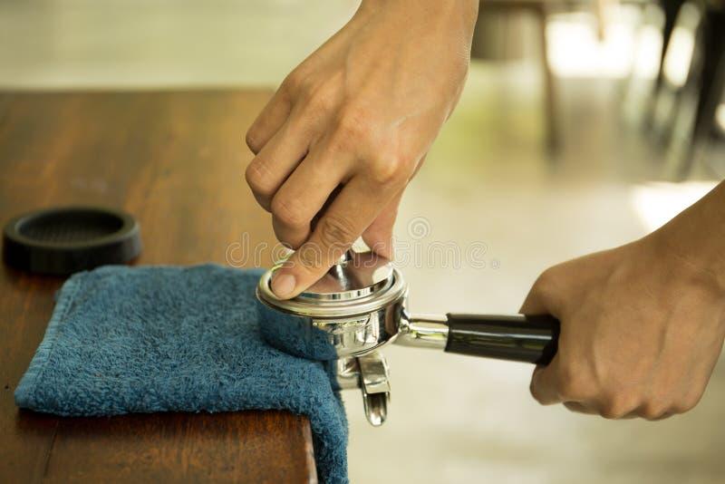 Barista que presiona el café molido en portafilter usando el pisón foto de archivo libre de regalías