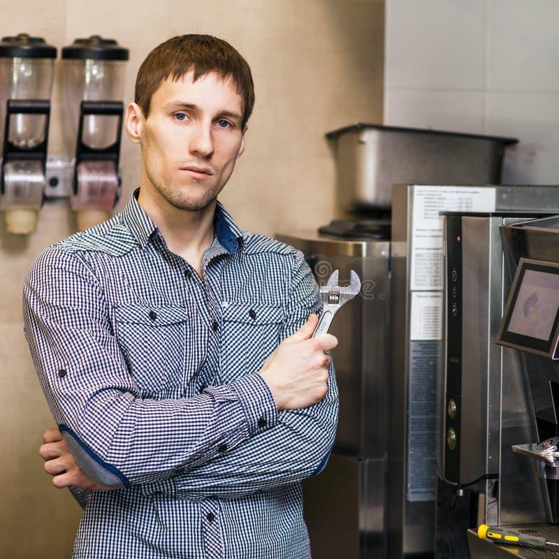 Barista que se coloca con la llave cerca de fabricante de café fotografía de archivo