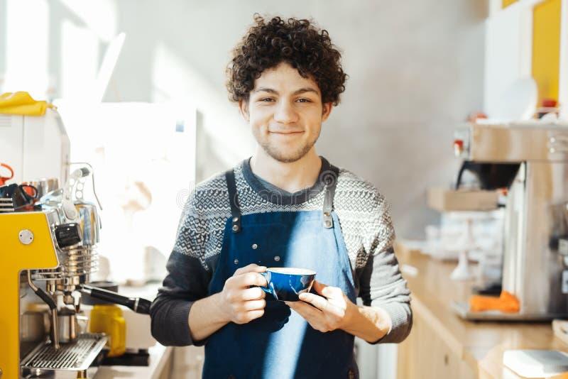 Barista que sonríe y que sostiene la taza de café cerca de contador de la barra en café moderno brillante foto de archivo libre de regalías