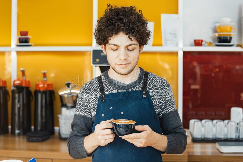Barista que sostiene la taza de café cerca de contador de la barra en café moderno brillante fotografía de archivo libre de regalías