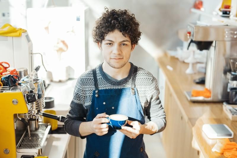 Barista que sostiene la taza de café cerca de contador de la barra en café moderno brillante fotos de archivo