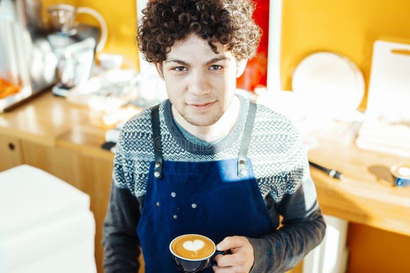 Barista que sostiene la taza de café cerca de contador de la barra en café moderno brillante imagen de archivo libre de regalías