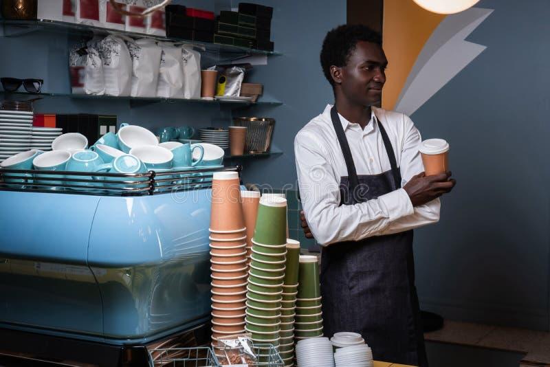Barista que sostiene una taza con café mientras que se coloca detrás de un contador en una cafetería y mira de lado fotos de archivo libres de regalías