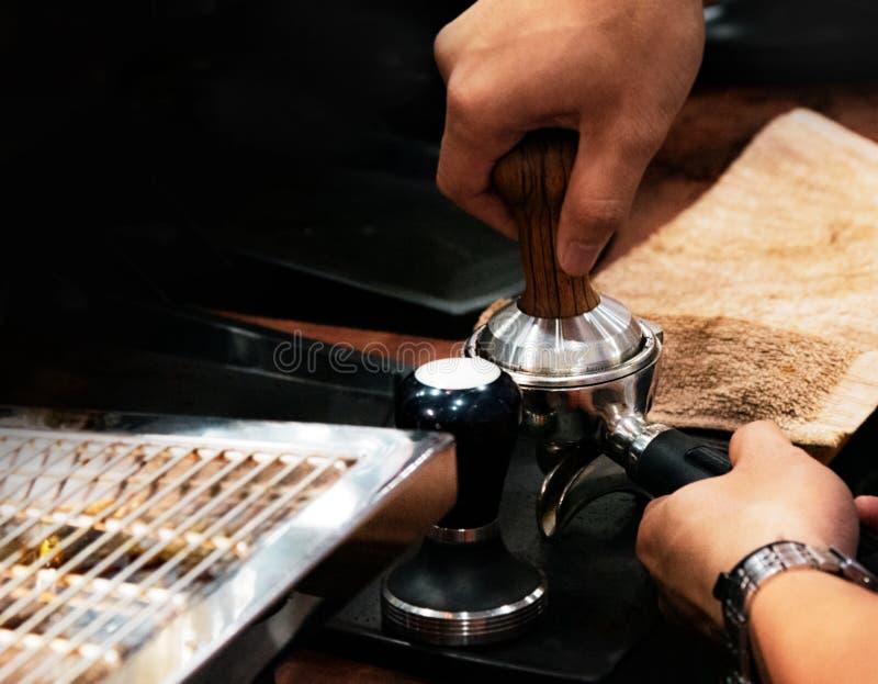 Barista que trabalha em uma cafetaria, fim acima do café à terra das imprensas do barista usando a calcadeira, conceito de Barist imagem de stock