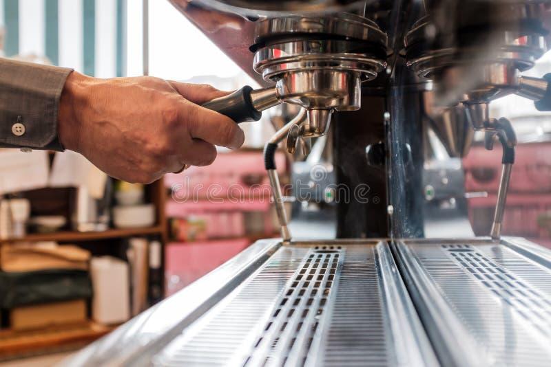Barista que trava o portafilter com café no grouphead do café m imagem de stock