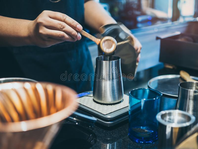 Barista`s hand putting ground coffee in stainless steel coffee grinder royalty free stock image