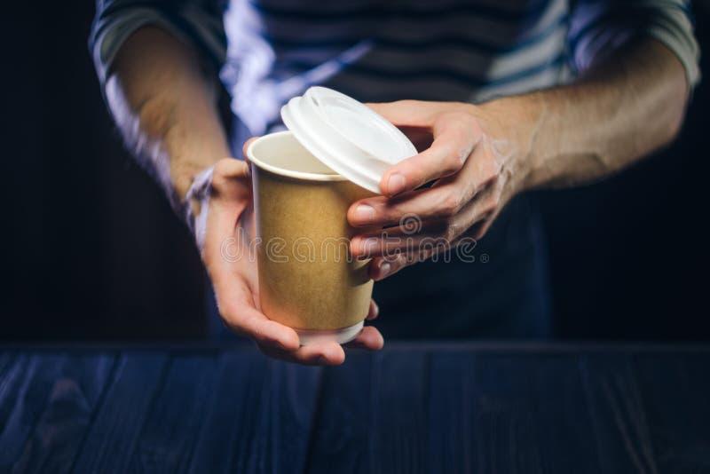 Barista sirve el café en una taza de papel en la barra fotos de archivo