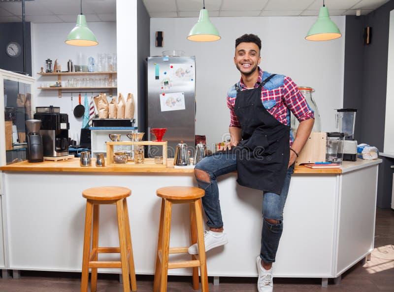 Barista sklep z kawą właściciela przystojnego mężczyzna uśmiechu szczęśliwy obsiadanie na barze zdjęcie stock
