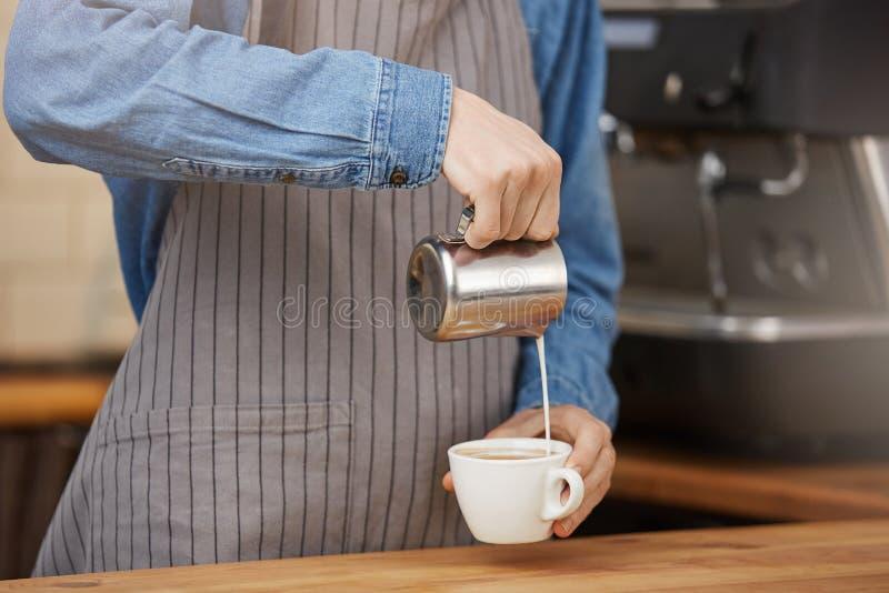 Barista som förbereder koppen av latte för kund i coffee shop fotografering för bildbyråer
