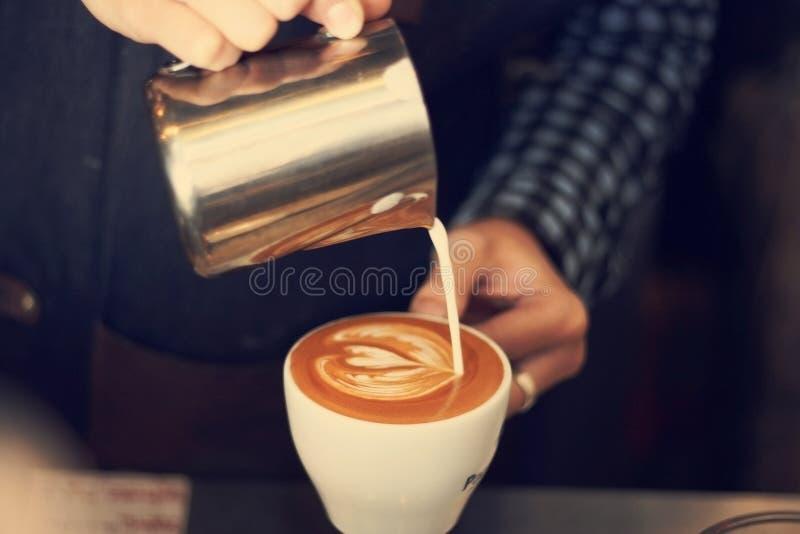 Barista som gör varm latte royaltyfria bilder