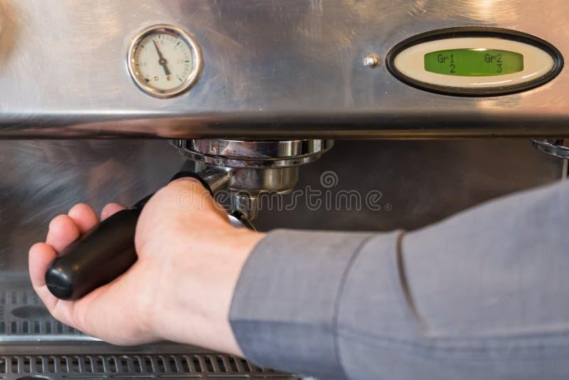 Barista som låser portafilter med kaffe i grouphead av kaffe M royaltyfria foton