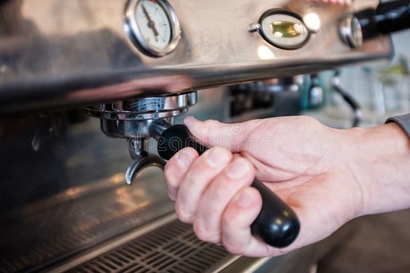 Barista som låser portafilter med kaffe i grouphead av kaffe M arkivbild