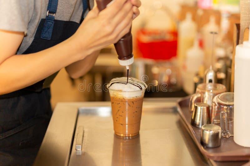 Barista som pressar chokladpralin på kräm i med is chokladdrink arkivbilder
