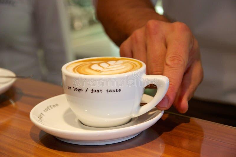 Barista som tjänar som nytt gjord latte på cafeterian royaltyfri foto