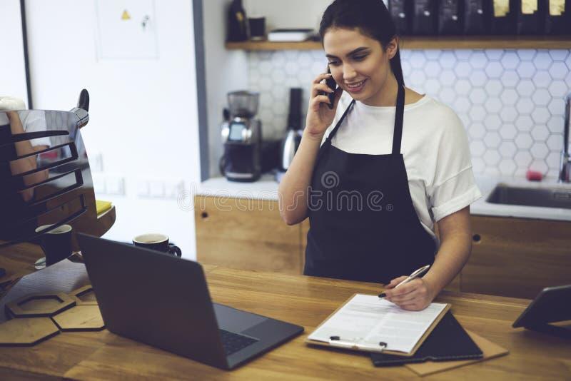 Barista sonriente que se coloca en la barra y que habla con el consultor del web sobre la comida que ordena para la cafetería fotografía de archivo libre de regalías