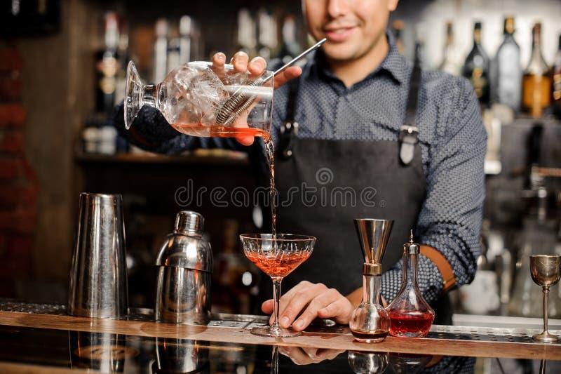 Barista sorridente che aggiunge bevanda alcolica rossa nel vetro di cocktail immagini stock